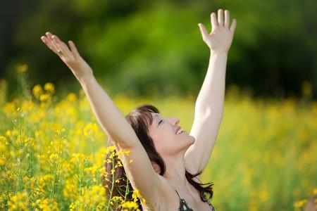 adult rape: happy woman breathing in yellow flower field Stock Photo