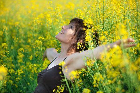 adult rape: mature woman lying in yellow flower field Stock Photo
