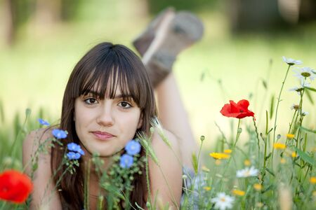 teen girl lying in wild flowers bed looking at camera photo