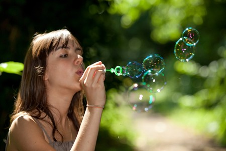 teen girl blowing bubble soap in park Stock Photo - 7150139