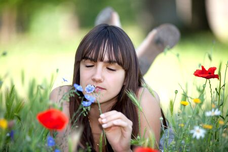 teen lying in meadow and smelling flowers at springtime photo