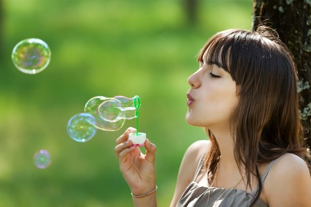 pretty teenage girl blowing bubbles soap in nature photo