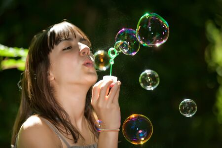 teenager blowing colorful bubble soap in nature photo