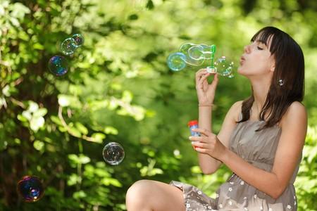 Teen Girl blowing Bubbles, die sitzen in frisch frühling Wäldern  Standard-Bild