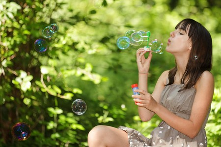 teen girl blowing bubbles sitting in fresh spring woods