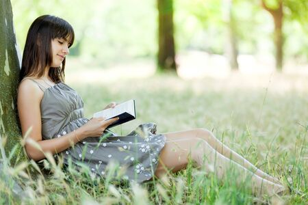 leant: teen girl reading book  leant against tree in park Stock Photo