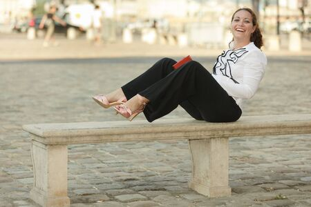 barefoot business woman sitting on stone bench and holding book photo
