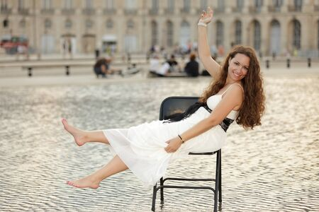 beautiful woman sitting on chair in flooded square in Bordeaux, France photo