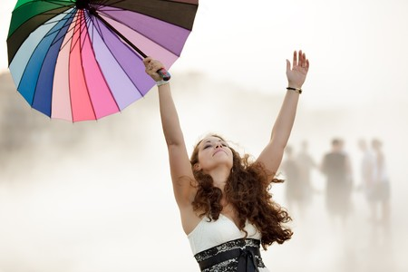 happy woman in heavy fog, holding colorful umbrella Stock Photo