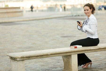 electronic organizer: business woman sitting on stone bench using electronic organizer and looking at camera