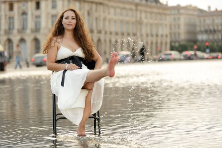 woman sitting on chair in flooded square in Bordeaux, france photo