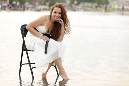 smiling beautiful woman sitting on chair in flooded square in Bordeaux, France photo