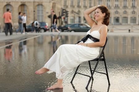 french model: smiling beautiful woman sitting on chair in flooded town center, Bordeaux, France