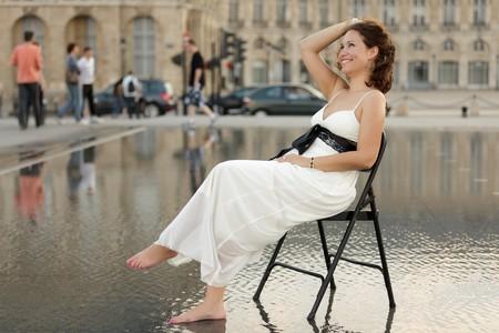 mujeres sentadas: sonriendo a hermosa mujer sentada en la silla en el centro de la ciudad inundada, Burdeos, Francia