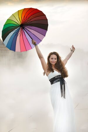 woman holding rainbow umbrella and raising arms in heavy fog photo