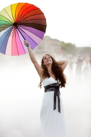 joyful pretty woman holding rainbow umbrella in fog photo