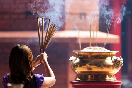 creed: woman holding smoking big incense sticks in chinese temple, Kuala Lumpur, malaysia Stock Photo