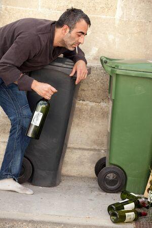drunk man standing on sidewalk and smoking cigarette photo