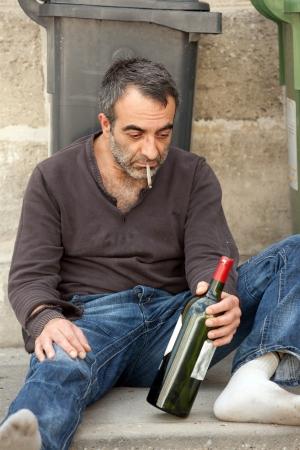 hobo: drunk man siitng on sidewalk near trashcan in city street