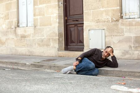 homeless lonely man lying on city street near house door photo