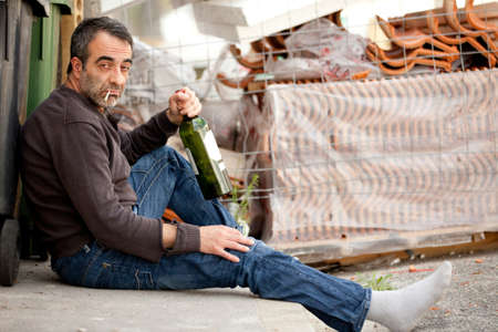 very sad man drinking wine on sidewalk near trashcan photo