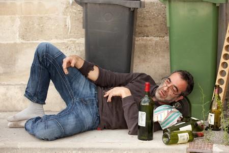 to degrade: pobre y borracho hombre tendido en la acera con botellas de vino cerca de basura puede