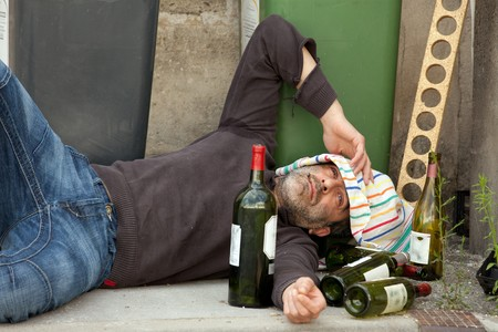 poor and drunk man lying on sidewalk  with bottles of wine near trash can photo