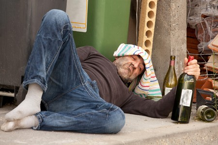 poor and drunk man lying on sidewalk  with bottles of wine near trash can Stock Photo