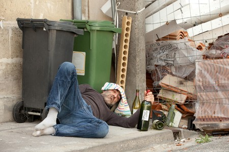 addiction alone: poor and drunk man lying on sidewalk  with bottles of wine near trash can Stock Photo