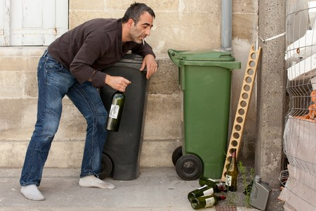 drunk man smoking cigarette and standing near trashcan