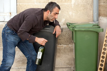 vagabond: very drunk man smoking cigarette on trashcan Stock Photo