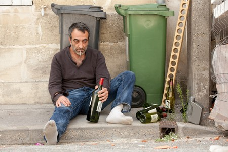 tramp: sad drunk man sitting on sidewalk near trashcan