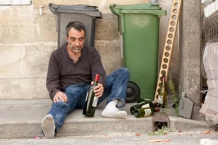triste homme ivre assis sur le trottoir près de poubelle  Banque d'images