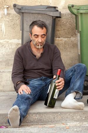 alcoholismo: triste hombre borracho sentado en la acera cerca de Papelera  Foto de archivo