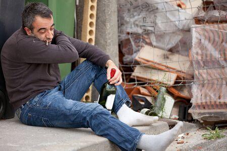 hombre sentado: hombre de vagabundo borracho sentado cerca de Papelera sosteniendo la botella de vino