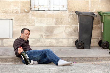 vagabond: drunk man lying on city street near trashcan Stock Photo