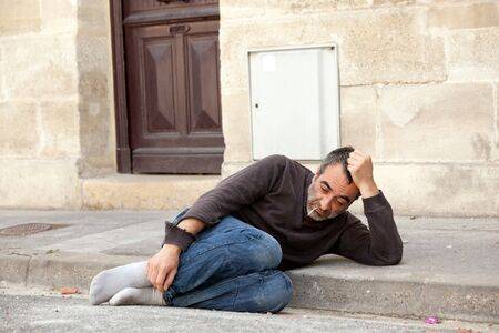 homeless man lying in city street near house door photo