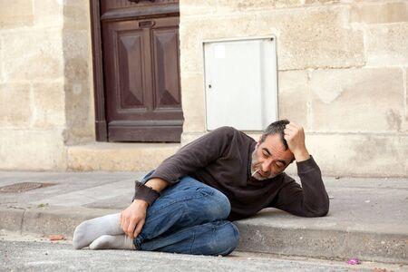 homeless man lying in city street near house door photo