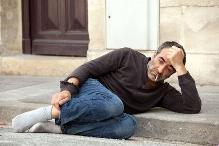 sad homeless man lying on sidewalk and smoking cigarette Stock Photo - 7713105