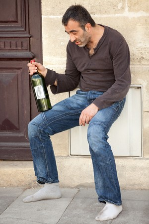 drunk alcoholic man standing near house entrance in the city photo