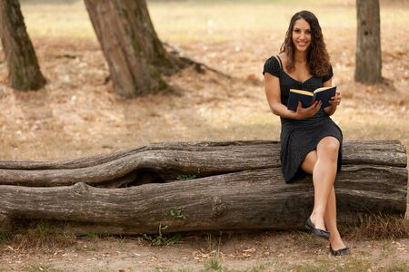 beautiful young woman reading in park sitting on tree trunk photo
