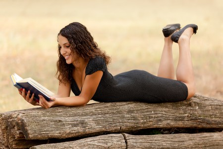 young beautiful woman lying on tree trunk reading book photo