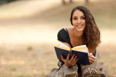 portrait of young woman reading book lying on tree trunk photo