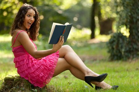 beautiful surprised woman reading book in nature photo