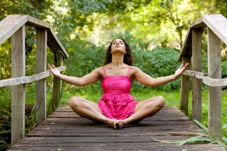 athletic woman in pink dress practicing yoga on wooden bridge in park Stock Photo - 7812723