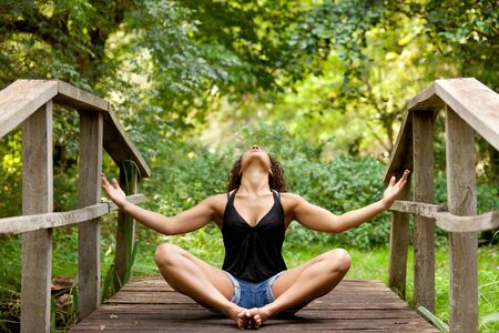 athletic woman in short jean practicing relaxation in nature photo