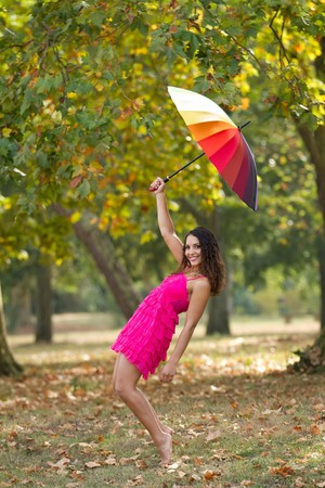 barefoot girl standing on tiptoe wearing pink dress with rainbow umbrella in park