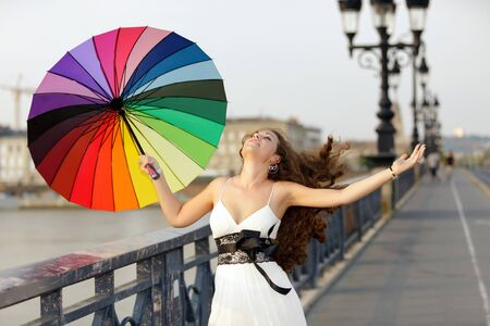 elegant woman walking on bridge with umbrella Stock Photo