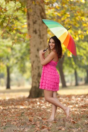 young woman holding rainbow umbrella walking in plane tree forest photo