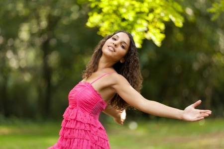 arms outstretched: young woman arms outstretched relaxing in park Stock Photo